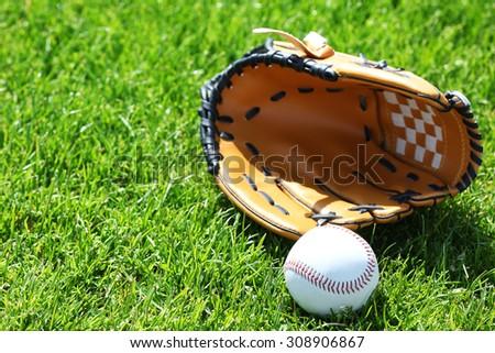 Baseball ball and glove on green field - stock photo