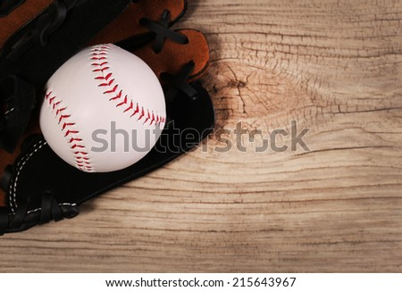 Baseball. Ball in Glove over wood background with copy space.  - stock photo