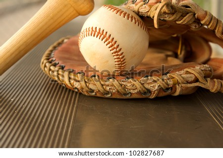 Baseball Bat and Glove on the bench of the dugout - stock photo