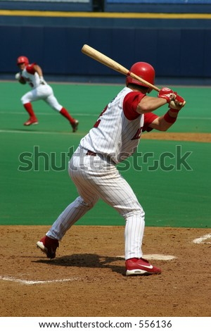 Baseball Batter waiting for his pitch, runner stealing second base in background - stock photo