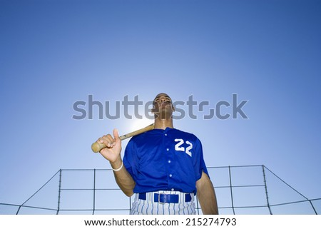 Baseball batter, wearing number �¢â�¬��22�¢â�¬â�¢ blue uniform, standing on pitch with bat resting on shoulder, front view, portrait, low angle view (backlit) - stock photo