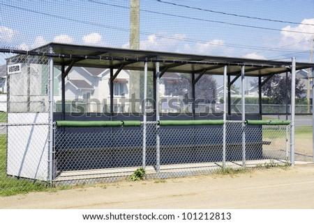 Baseball dugout at the local outdoor stadium with net and mesh to protect the players while they wait their turn to bat while sitting on the bench. - stock photo
