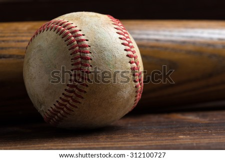 Baseball equipment: wooden bat and ball on a wood plank or bench background - stock photo