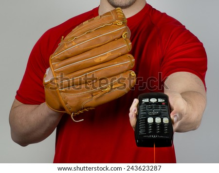 Baseball glove and tv remote control. - stock photo