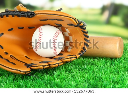 Baseball glove, bat and ball on grass in park - stock photo