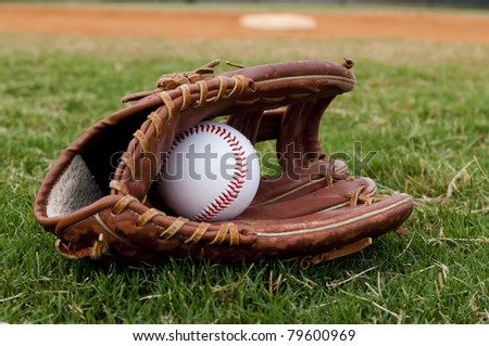 Baseball in old glove on field with base and outfield in background. - stock photo