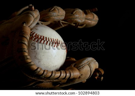 Baseball mitt and vintage hardball in black - stock photo
