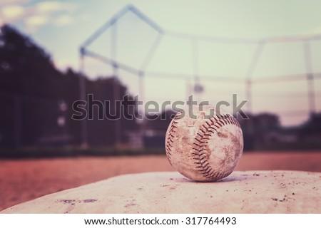 Baseball on a base. Vintage Instagram effect. - stock photo