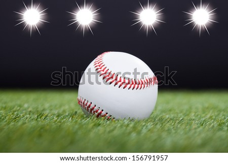 Baseball On Grass Field With Light In The Background - stock photo