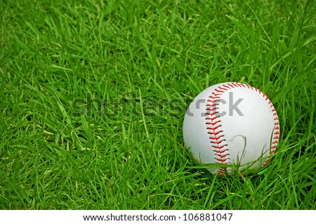 baseball on green grass pitch with copy space - stock photo