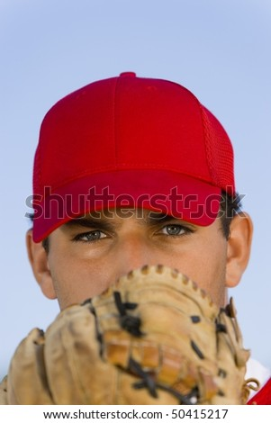 Baseball pitcher holding glove in front of face, (close-up), (portrait) - stock photo