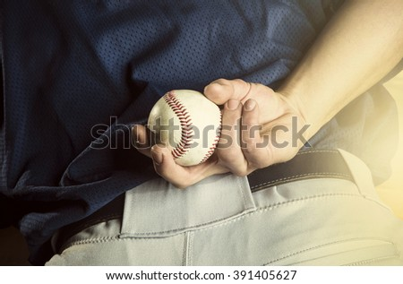 Baseball pitcher ready to pitch. Close up of hand focus on the fingers and the ball - stock photo