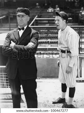 Baseball player and umpire - stock photo