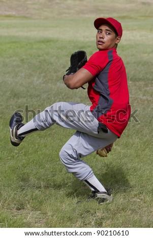 Baseball player mid-pitch - stock photo