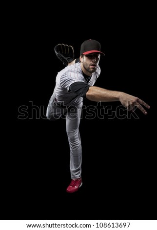 Baseball Player pitching a ball on a black background. - stock photo