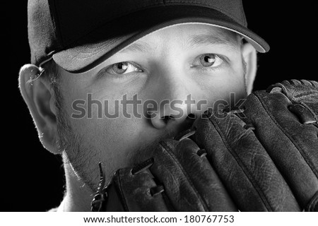 Baseball Player - This is a black and white photo of a young man wearing a baseball cap and looking out over his glove. Shot on an isolated white background and processed slightly to enhance detail. - stock photo