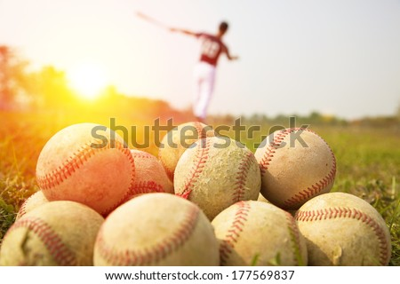 Baseball players practice wave a bat in a field - stock photo