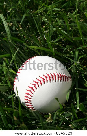 Baseball sitting on a field - stock photo