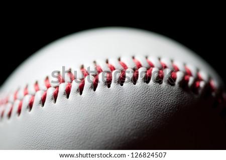 Baseball stitch, macro shot, black background - stock photo