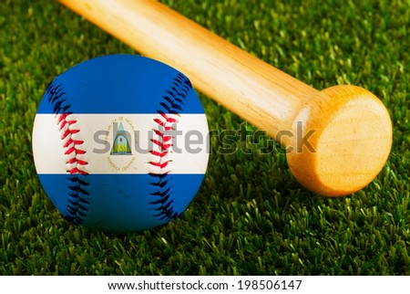 Baseball with Nicaragua flag and bat over a background of green grass - stock photo