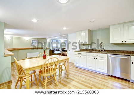 Basement kitchen room with rustic dining table set in Mother-in-law apartment. Light mint tones of wall blent with white kitchen cabinets - stock photo