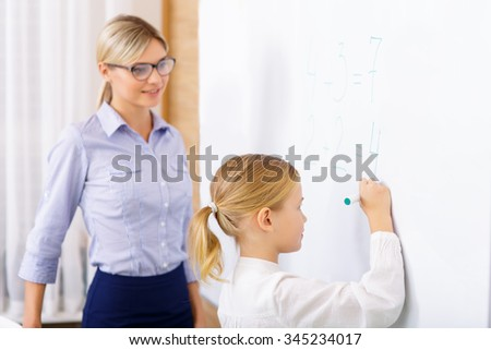 Basic math. Young good-looking teacher is helping little girl to solve basic math equations.  - stock photo