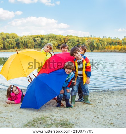 Basic school students in rainwear with umbrellas - stock photo