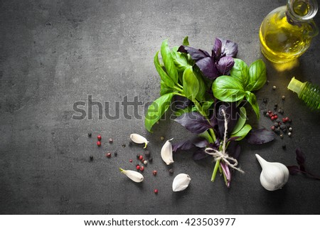 Basil leaves, garlic, pepper and olive oil at dark slate background. Space for text. Ingredients for cooking. - stock photo