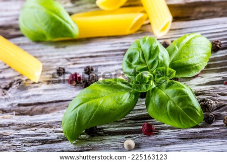 Basil leaves pepper and  pasta on a old wooden table - stock photo
