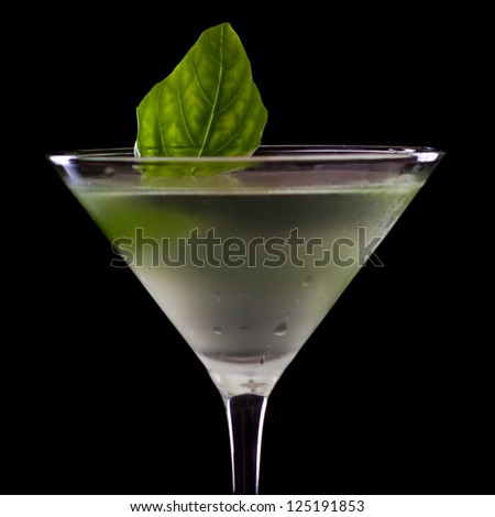 basil martini isolated on a black background with a fresh leaf garnish - stock photo