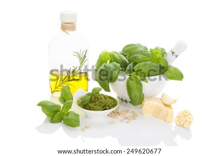Basil pesto, fresh basil leaves in mortar, garlic, parmigiano cheese and extra virgin olive oil isolated on white background. Culinary eating. - stock photo