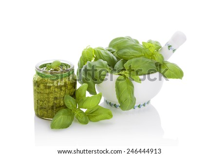 Basil pesto in glass jar and fresh basil leaves in mortar isolated on white background. Culinary eating. - stock photo