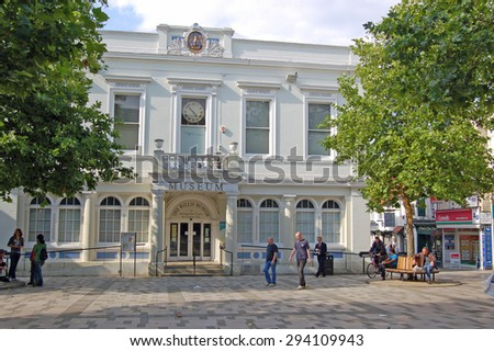 BASINGSTOKE, UK - AUGUST 7, 2007: Pedestrians enjoying the late afternoon summer sunshine at the historic market place in Basingstoke dominated by the town's Willis Museum.  August in Hampshire. - stock photo