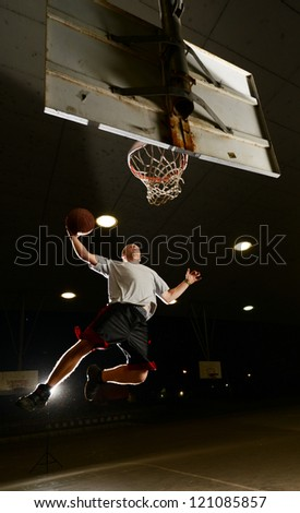 Basket and basektball player jumping with ball and aiming at basket at night - stock photo