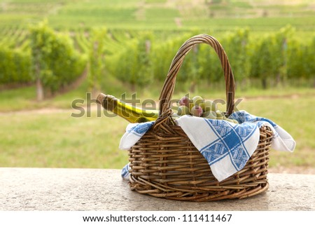 Basket and bottle of white Pinot wine in front of a vineyard in Alsace, France - stock photo