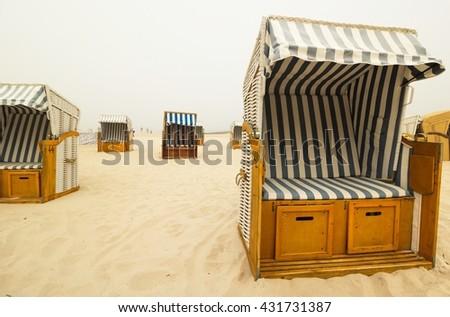 Basket Chairs on a foggy beach, Baltic sea - stock photo
