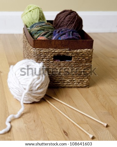 Basket full of yarn, chunky wool and knitting needles - stock photo