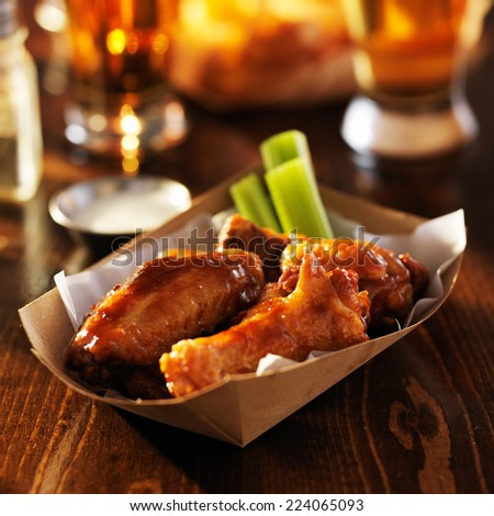 basket of barbecue buffalo chicken wings with celery sticks and ranch sauce  - stock photo