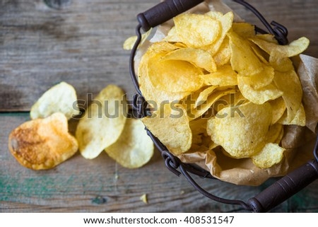 basket of chips on a shabby wooden background - stock photo