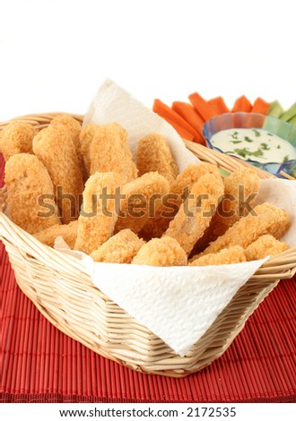 basket of crispy chicken fingers with platter of vegetables and dip - stock photo