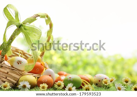 Basket of easter eggs on meadow,Closeup. - stock photo