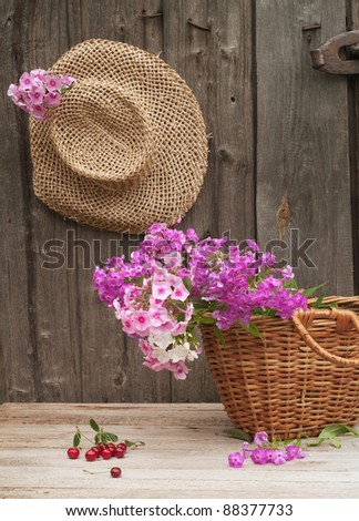 basket of flowers and a straw hat against the background of the old wooden walls - stock photo