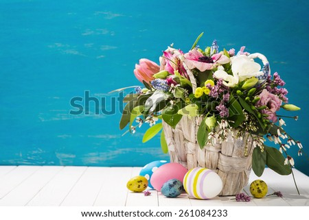 Basket of flowers and easter eggs on a wooden background with space for text. - stock photo