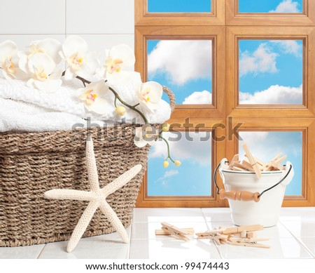 Basket of fresh laundry with clothespins against a blue sky window - stock photo