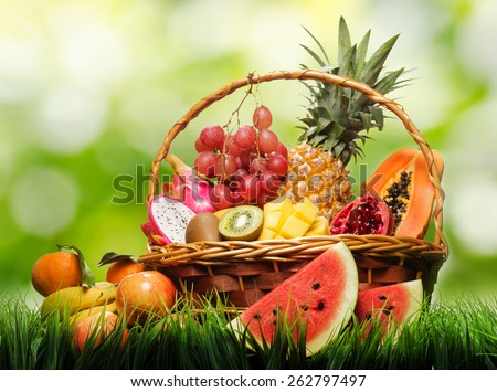 Basket of fresh tropical fruits on green grass and on nature background. Pineapple, papaya, mango, kiwi, grape, garnet, tangerines, bananas, apples, watermelon slices, pitaya or dragon fruit. - stock photo