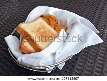 Basket of freshly baked pastries and two pieces of toast  including Pain aux Raisins - stock photo