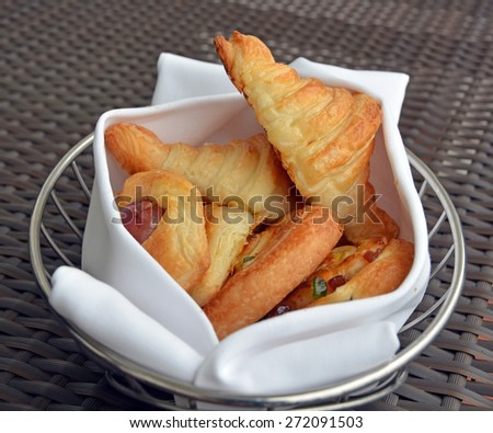 Basket of freshly baked pastries including Croissants and Pain aux Raisins wrapped in a white cloth - stock photo