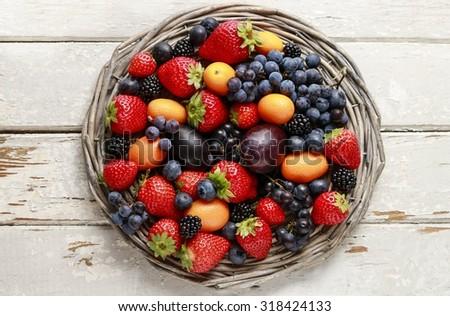 Basket of fruits: strawberries, blueberries, blackberries, grapes and kumquats.  - stock photo