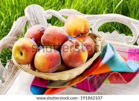 Basket of peaches on wooden tray. Summer garden party idea - stock photo