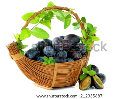 Basket of plums on white background - stock photo